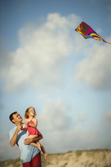 Man and his daughter playing with a kite at the beach.
