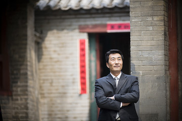 Mid-adult businessman standing with his arms folded.