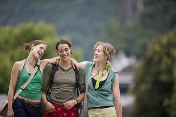 Three smiling female tourists walking along an urban street.