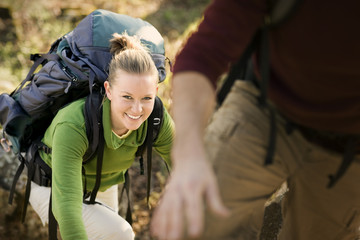Portrait of a young adult woman climbing with a backpack outside.