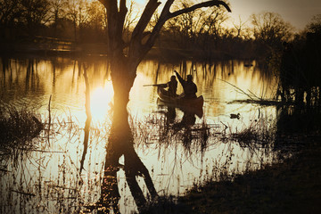 Couple duck shooting on a lake at sunset.