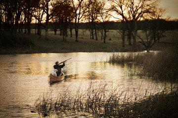 Man and his dog on a canoe with a gun along a river at sunset.