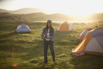 Portrait of a laughing young woman throwing a football in a campsite at sunset.