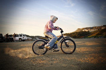Boy in a hooded shirt skidding while riding a bicycle in a carpark near the beach.