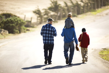 Grandfather walking with his son and grandsons along a country road.