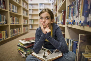 Thoughtful teenage girl reading books in a library.