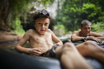 Portrait of boy and his father sitting in inflatable rings on a river.