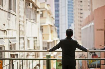 Businessman observing an urban scene.