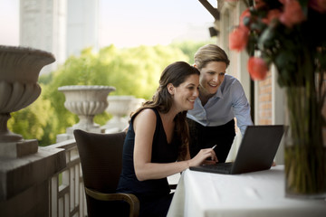 Two businesswomen using a laptop outside on a balcony.