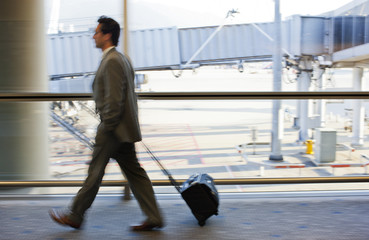 Mid-adult businessman pulling a suitcase while rushing through an airport.