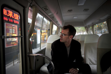 Mid-adult man sitting alone inside a small bus.