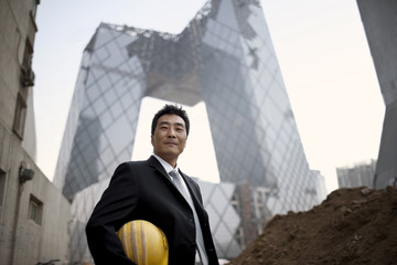 Portrait of a mid-adult businessman holding a hard hart while standing in a construction site.