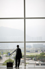 Businessman looking at the view over airport buildings.