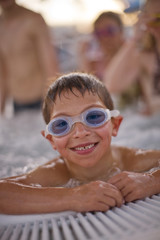 Portrait of a smiling young boy wearing swimming goggles in a swimming pool with others.