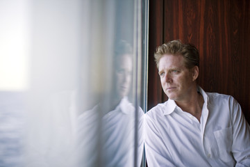 Mature man looking contemplatively out a window.