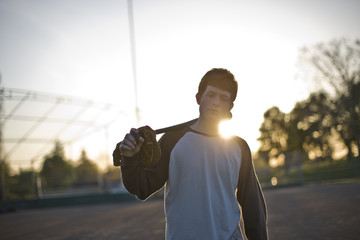 Portrait of a teenage boy carrying a baseball mitt and baseball bat over his shoulder in the sunlight.