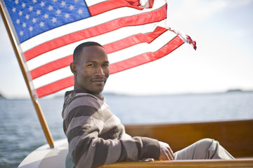 Young man on boat next to American flag