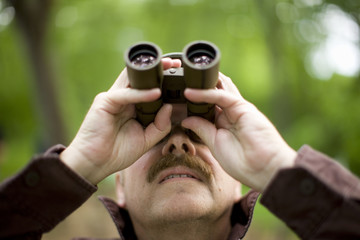 Man looking upward through binoculars