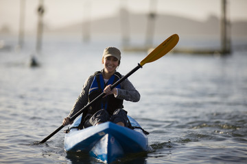 Portrait of a smiling mid-adult woman paddling in a kayak.