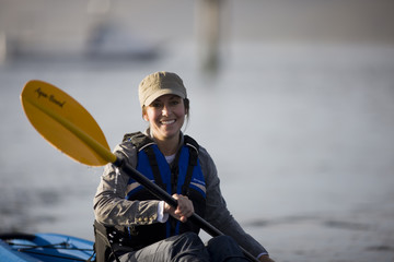 Portrait of a smiling mid-adult woman while sitting in a kayak.