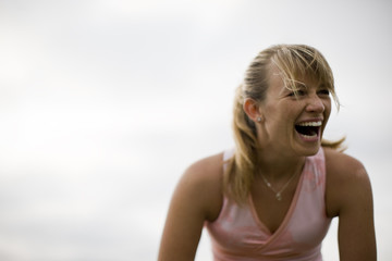 Teenage girl laughing while outside.