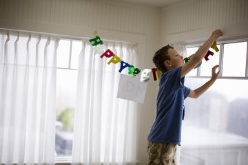 Boy hanging a 'Happy Birthday' sign