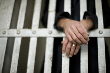 Hands of a mature businessman through bars of a cell in a derelict building.