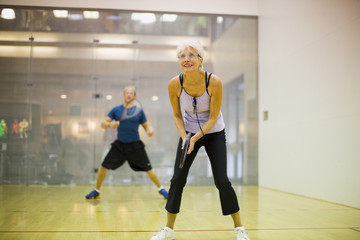Senior woman playing squash with a mid-adult man.