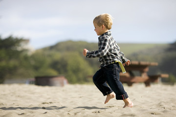 Young boy running along a beach.