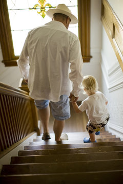 Father helping his young son to walk down a wooden staircase.