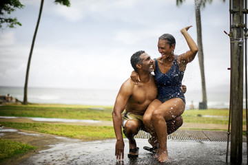 Couple showering under beach shower