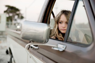Young girl staring out the window in the passenger seat of a pickup truck.