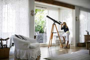 Young girl looking through a telescope from her living room.