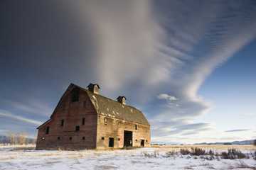 Abandoned barn in a snowy field