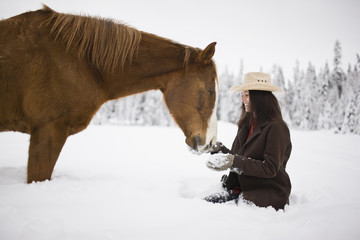 Young woman kneeling in the snow patting horse