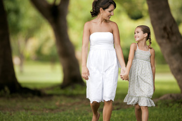 Mother and daughter holding hands in park
