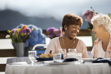 Two mature female friends smile happily at each other as they enjoy a meal at an outdoor restaurant table.