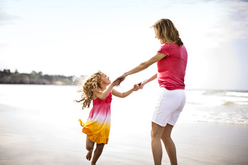 Mother and daughter dancing at the beach.