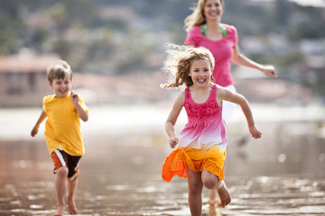 Family running along the beach.