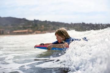 Boy riding a wave on boogie board.