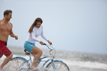 Man running alongside a woman on a bike at the beach.