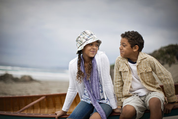 Young siblings sitting together at beach.