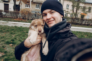 man taking selfie with adorable brown puppy with amazing blue ey