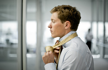 Young businessman tying his tie in his office.