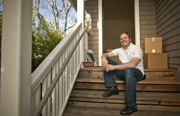 Smiling man sits outside new house