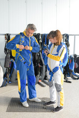 Man and woman putting on jumpsuits