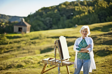 Portrait of a senior woman painting a canvas in a rural setting.