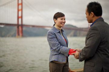 Smiling young woman seals a business deal with a handshake in front of the Golden Gate Bridge.