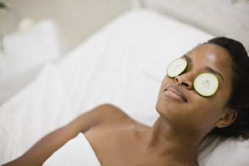 Young woman lying on her back in bed with cucumber slices over her eyes.