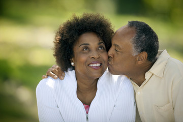 Happy mature man gives his smiling wife a kiss on the cheek.